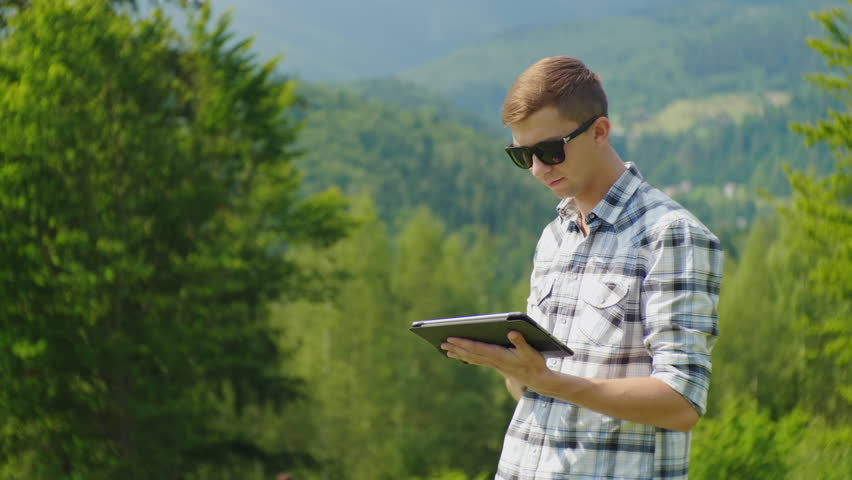 A young man uses a tablet, stands in a picturesque place against a background of green leaves #29275822