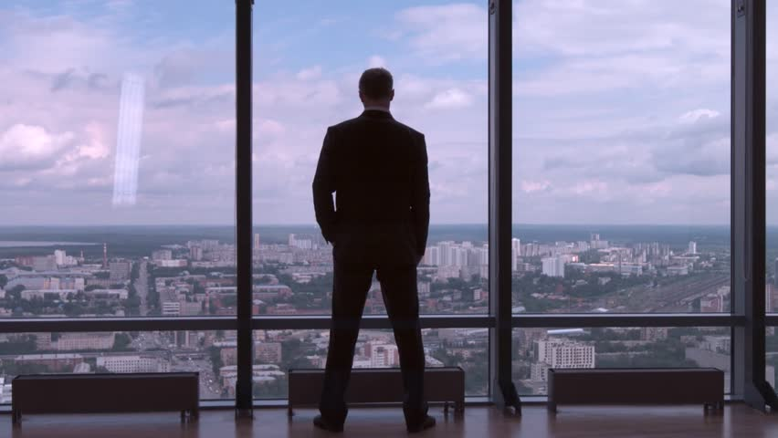 Full length back view of successful businessman in suit standing in office with hands on waist, CEO. Businessman from the back in front of a city view on the window | Shutterstock HD Video #29280913