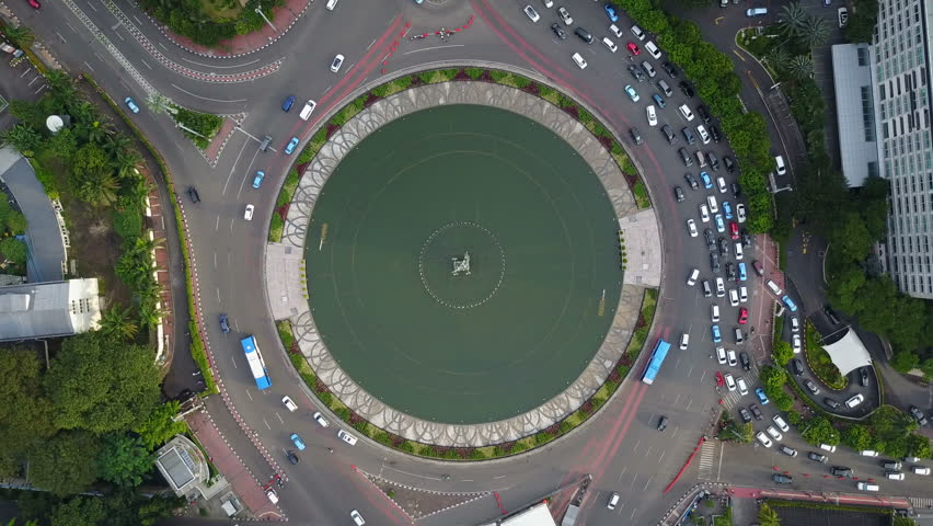 JAKARTA, INDONESIA - APRIL 2017: Overhead static drone shot of roundabout and fountain in central Jakarta, Indonesia