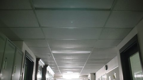 point of view of ceiling and fluorescent lights walking down school university high school hallway past lockers to class lecture in slow motion