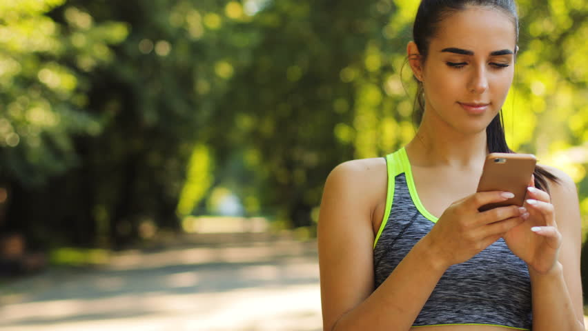 Attractive young woman preparing her smart phone for the future running. Close up shot.