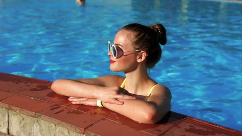 An adult and attractive girl in stylish sunglasses, dressed in a swimsuit, is in the pool on a hot summer day, the lady relaxes and rests on her vacation