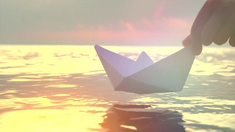 Kid putting a paper boat into water over beautiful sunset. Little boy's hand puts paper ship on sea surface. Origami ship Sailing. Dreams, future, childhood, freedom or hope concept. Slow motion 4K