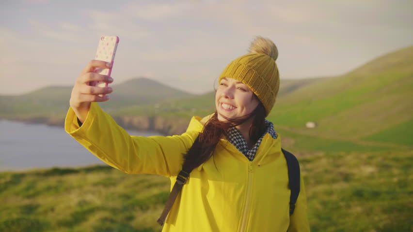 Smiling Female Tourist Taking Selfie With Smartphone On Mountain