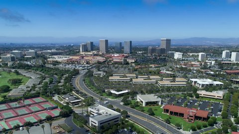 Aerial timelapse in motion (hyperlapse) from a drone of Fashion Island shopping center skyline in Newport Beach, California with office buildings, traffic, mountains and clouds overhead.