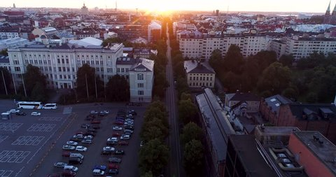 Aerial scenic view of Helsinki capital of Finland during sunrise. Drone flying forward above rooftops filming straight street line of Bulevardi ending at morning sun. Scandinavia