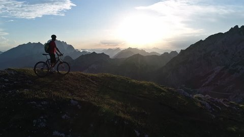 Aerial - Flyover mountain biker standing on top of the mountain at sunset