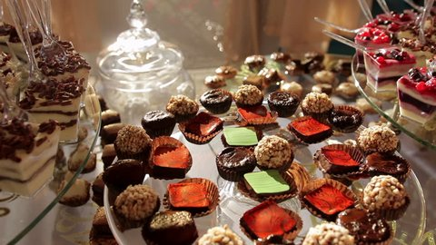 Delicious wedding reception candy bar dessert table inside of the celebration hall. Curtains and the wall on the background. Close-up. Steadycam. No people