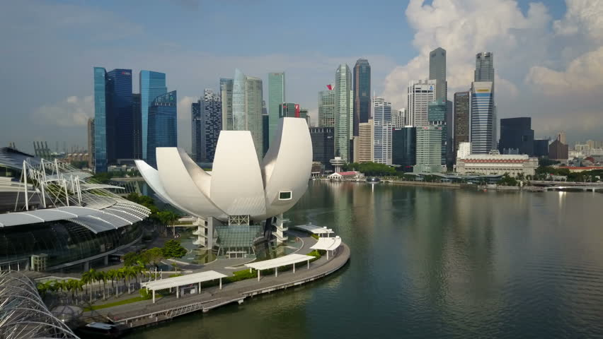 SINGAPORE - MAY 2017: Aerial drone shot flying over Lotus flower building of science museum towards modern skyline financial and business district at Marina Bay in Singapore