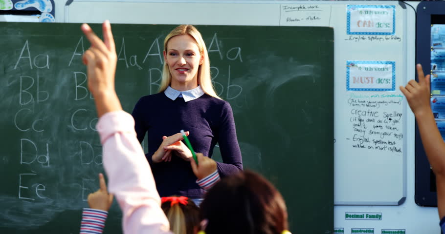 Front view of Caucasian teacher asking questions to her students in classroom at school