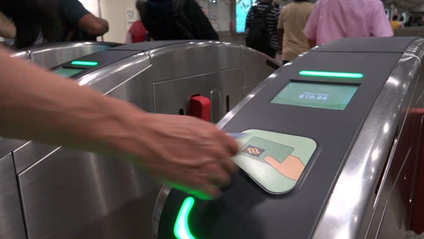 SINGAPORE - MAY 2017: Commuting subway passengers swipe cards to exit MRT (Mass Rapid Transit) station via turnstiles in Singapore