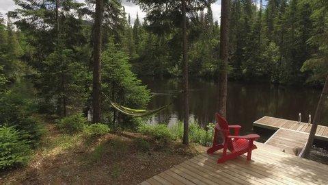 beautiful scene of muskoka chairs and hammock at lake cottage