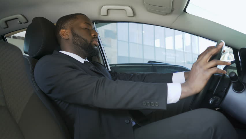 African-American Man In Suit Sitting In Car And Yawning