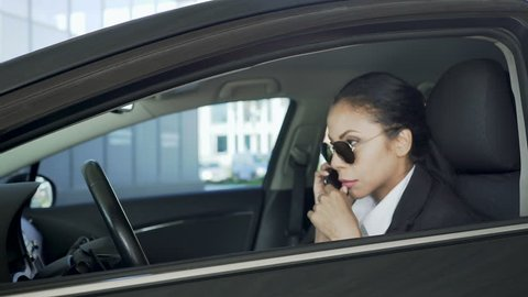 Lady in sunglasses, sitting in car and talking over cellphone, police agent
