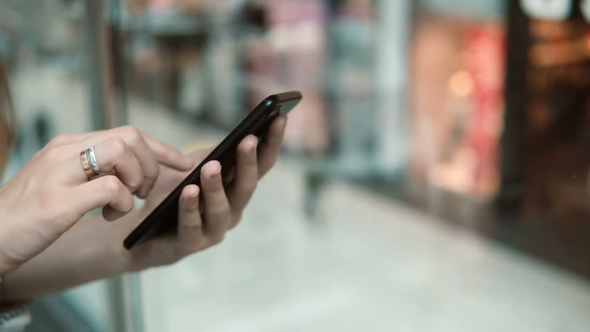 Close-up view of female hands holding smartphone, using the touchscreen technology. Woman spending time in shopping mall