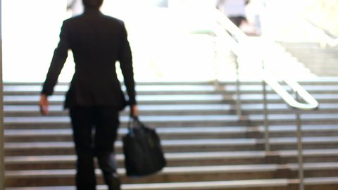 crowd of business commuters climb stairs
