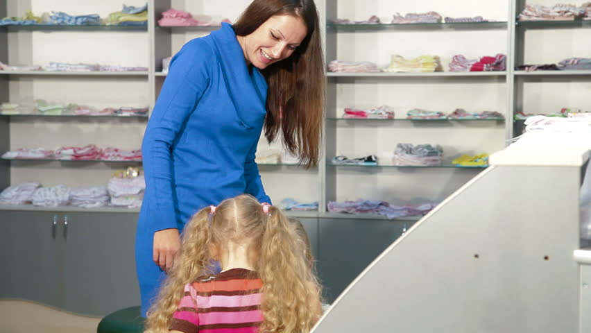 Mother with two daughters shopping for girls clothes in a clothing store, looking kids underwear