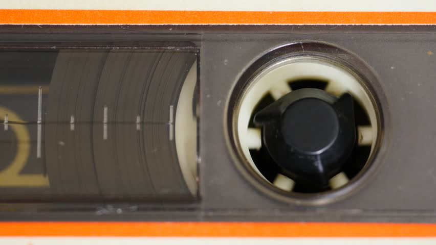 Close up of audio cassette tape in use sound recording in a cassette player.