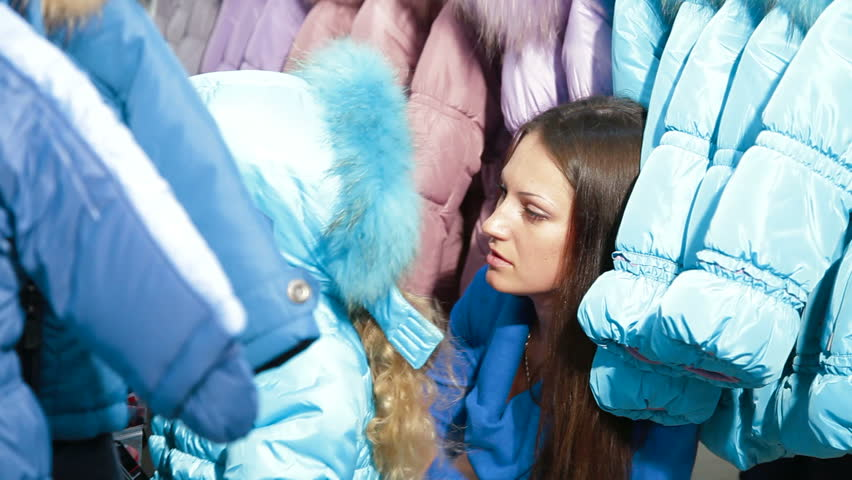 Mother and daughter shopping for clothes in a clothing store, child trying on winter coat