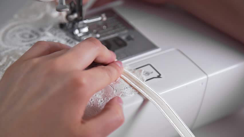 Tailor sews lingerie on a sewing machine, thread and lace, handmade underwear and clothes, sewing machine at work process, work in a sewing studio | Shutterstock HD Video #29477683