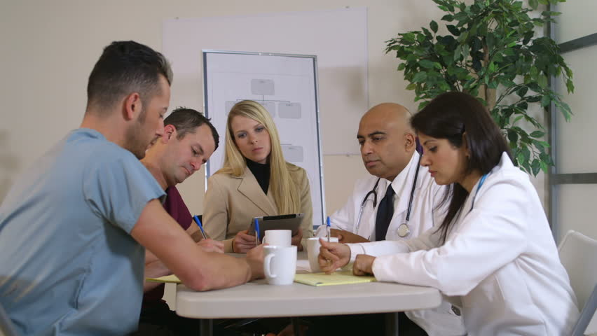 Lovely blond pharmaceutical saleswoman and group of doctors sitting at a table listening to her presentation. Canon C300
