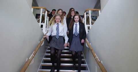 4K Tracking shot of happy students walking through school building, going home at end of day
