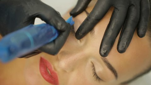 Cosmetologist making eyeliner permanent make up