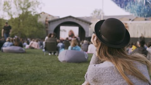 Back view of young stylish woman in hat sitting in bag-chair and looking movie in open-air cinema festival alone.