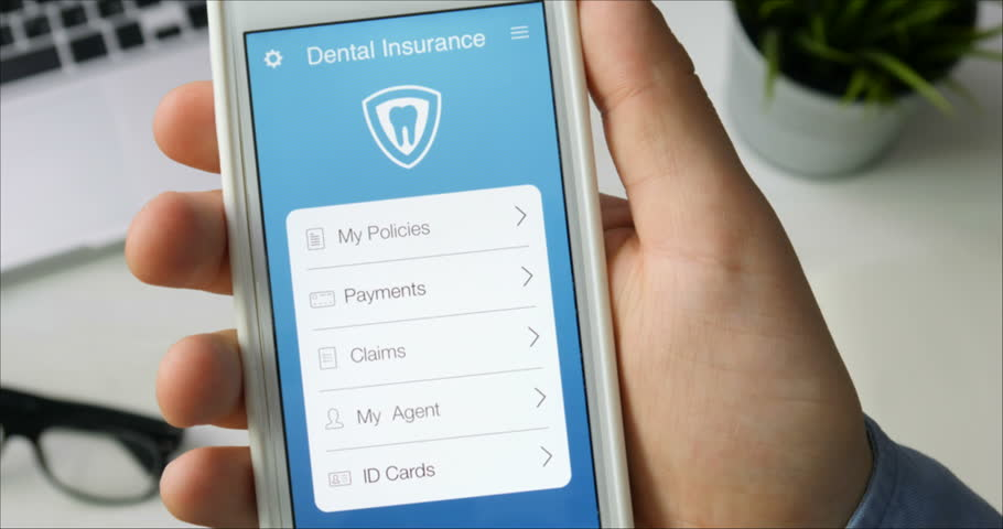 Paying for dental insurance using smartphone app sitting at the desk | Shutterstock HD Video #29520913