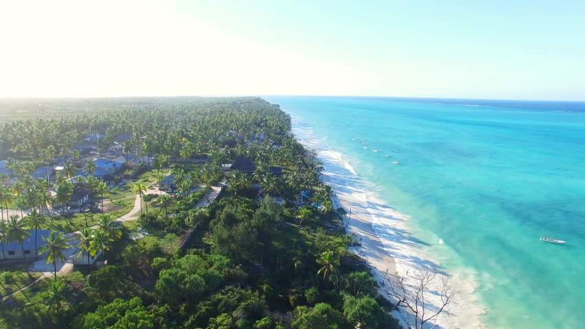 Aerial view of tropical paradise beach with white sand and turquoise crystal clear water of blue lagoon at sunset, a lot of palm trees on shore - Paje, Zanzibar, Tanzania, Africa, Indian Ocean, 4k UHD