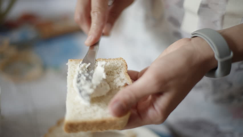 Female hands making a sandwich. Putting cheese on bread. Close-up.