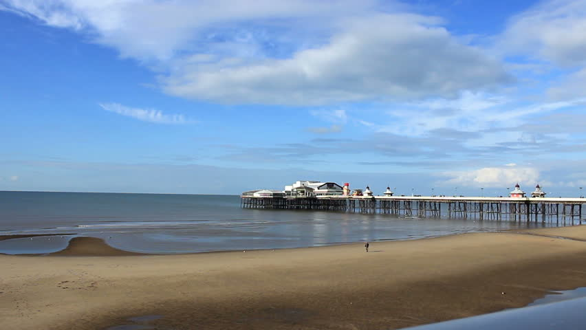 North Pier Blackpool and panoramic view of the beach and people walking around. Blackpool is a popular seaside resort on the Lancashire coast in North West England.