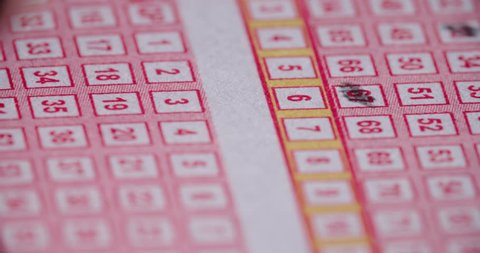 Lotto Ticket Pencil in Numbers Down Close Up. a close up of the tip of a pencil filling in lotto number boxes moving from right to left