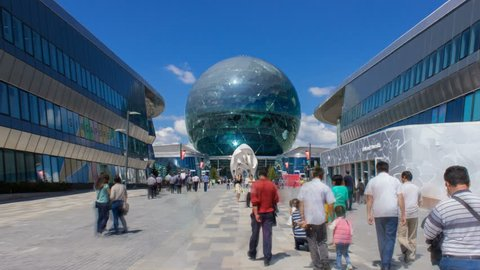 Kazakhstan, Astana, July 19, 2017. People walk through the territory of Astana EXPO.Nur Alem pavilion. Day time motion timelapse at the Astana Expo 2017, with a cloudy sky.