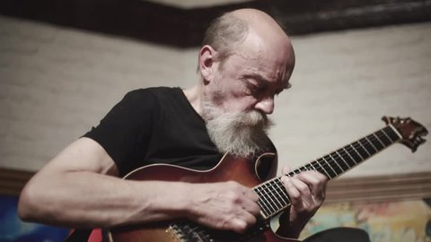 An elderly man with a gray beard skillfully plays the electric guitar, the guitarist plays against the background of abstract paintings, a seven-stringed electric guitar, a man plays with inspiration