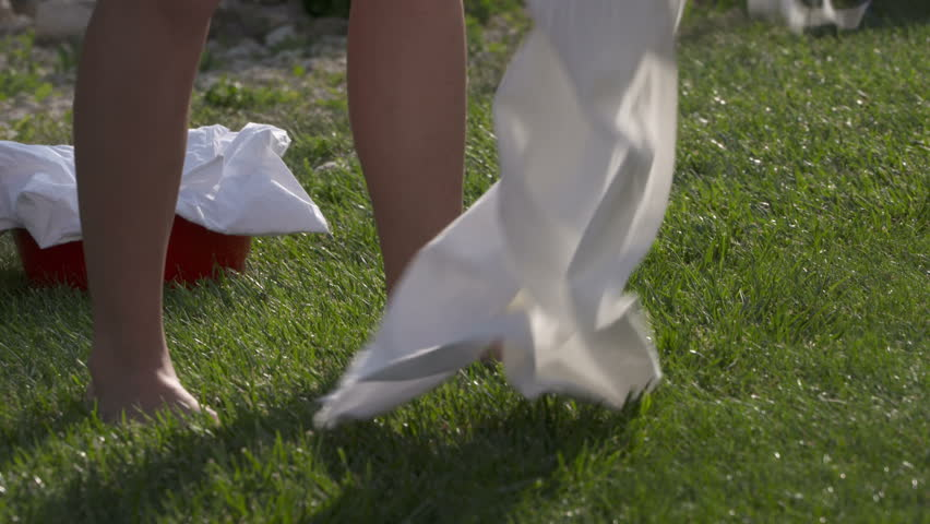 Young girl taking dry clean clothes off the clothesline outside. Close-up of bare female feet legs on grass and dried white sheets in laundry basket.