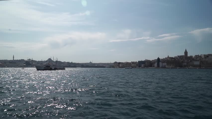 ISTANBUL, TURKEY, MAY, 2017: Coastline of Galata District with famous touristic landmark Galata Tower, boats passing under Galata Bridge, that spans the Golden Horn in Istanbul, Turkey.