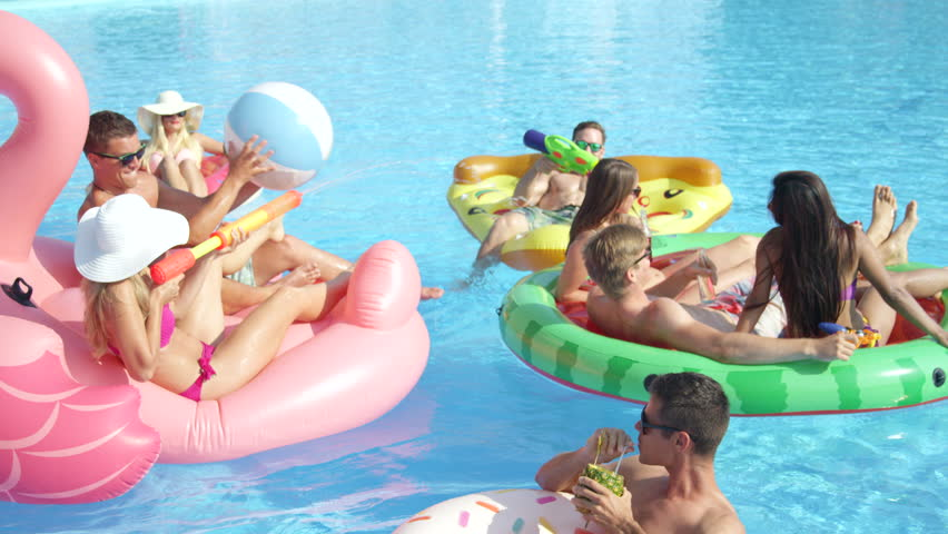 SLOW MOTION CLOSE UP: Playful smiling friends enjoying hot summertime on colorful floaties at pool party. Cheerful young people having fun on inflatable pizza, flamingo, watermelon and doughnut floats