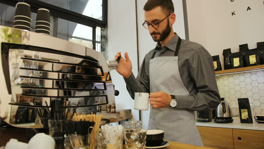 Portrait of attractive barista in the glasses preparing cup of coffee for customer in modern coffee shop. View from the side.