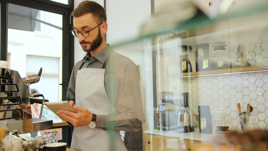 Portrait of male hipster barista using tablet at the work day in the coffee shop and smiling on camera. View from the side.
