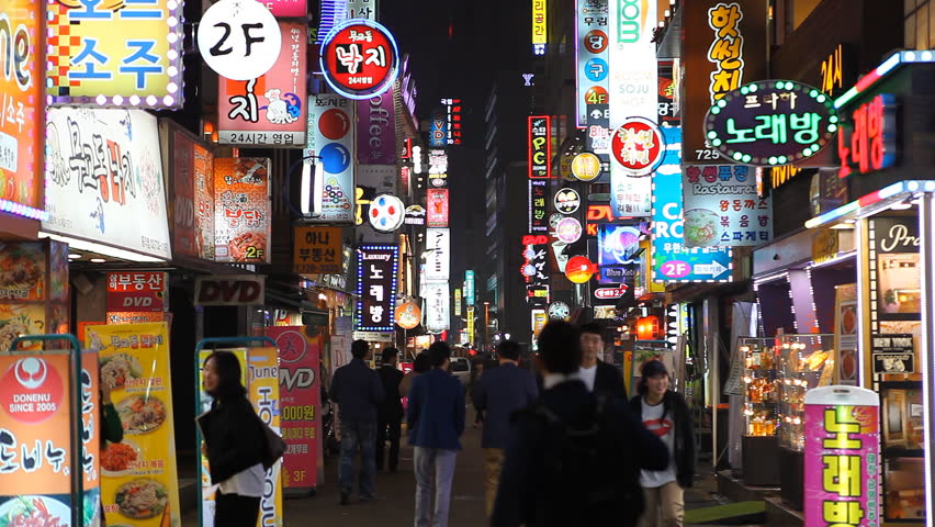 SEOUL, SOUTH KOREA - APRIL 22, 2012 Seoul City Neon Electronic Signs Street by night, Asian Shopping, Busy Shoppers in South Korea Evening Illuminated