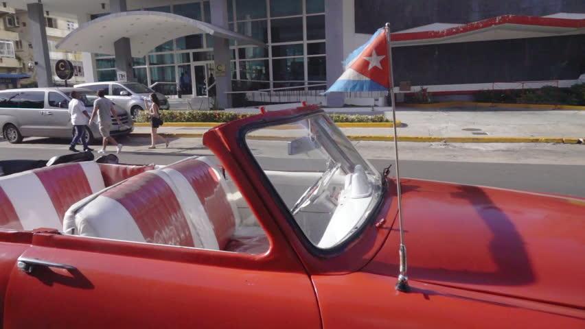 vintage taxi car and cuban flag In slow motion Havana, Cuba