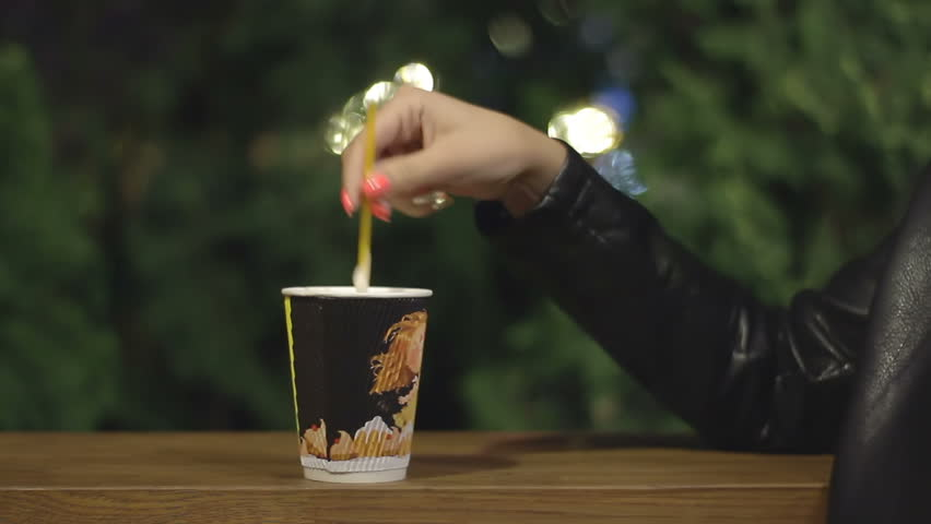 The woman is drinking coffee. A girl spends time alone. Hand stirs cappuccino in a paper cup | Shutterstock HD Video #29713873