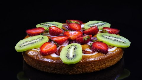 Excellent side-view of round pie with sliced fresh strawberries and kiwi-fruit, rotating concentric clockwise. Amazing dessert with yummy juicy fruit on black background with vibrant texture in 4k.