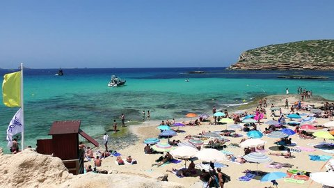 IBIZA, SPAIN - JUNE 26: Many tourists at Cala Conta beach on June 26, 2017, in San Antonio, in Ibiza Island, Spain. Ibiza is a famous summer tourist destination in Europe