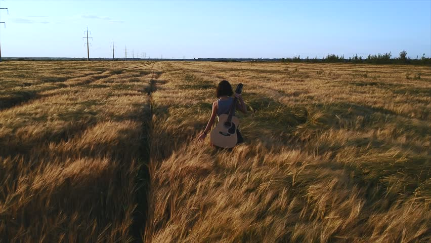 happy girl walking with a guitar at wheat field