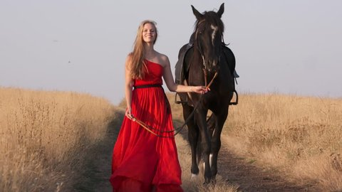 Young girl in long red dress leading saddled black horse in countryside. Beautiful horsewoman with her stallion walking down a dirt road in summer evening.