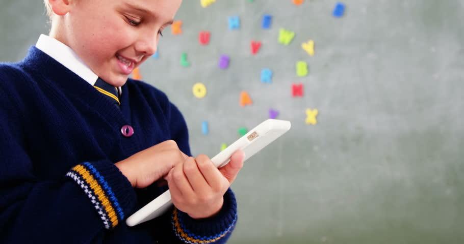 Simple smiling schoolboy using digital tablet in classroom - Wandtafel kuche ...