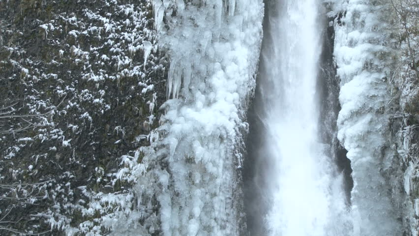 Icicles formed on flowing waterfall after winter storm.