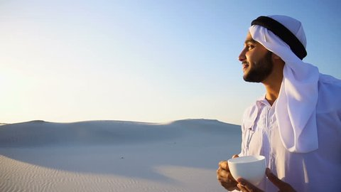 Portrait  confident and happy male Arabian Sheikh Muslim who drinks invigorating coffee drink from white cup and enjoys calm morning, standing in midst of endless sandy desert with pure white sand i